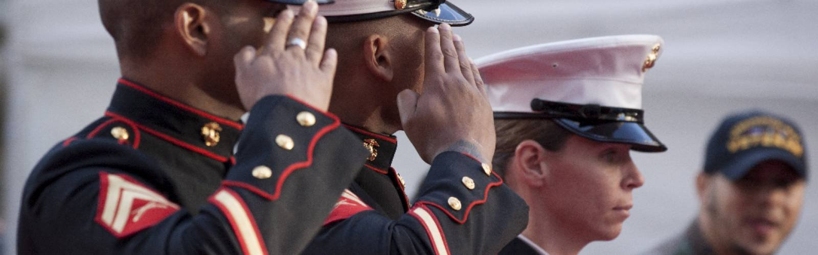Two men and a woman in U.S. Marine Corps dress uniforms salute.