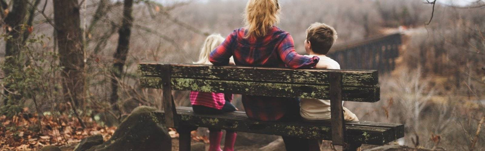 Photo credit: Benjamin Manley. A woman wearing flannel sits on a bench with two young children, back to the viewer.