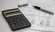 Photo of a calculator, papers and pens on a table