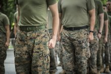 A picture of the torsos of several people wearing camoflague pants and olive drab t-shirts.
