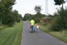 A photo of a family, taken from the back. A man in a green shirt pushed someone using a wheelchair, while walking with a small child.