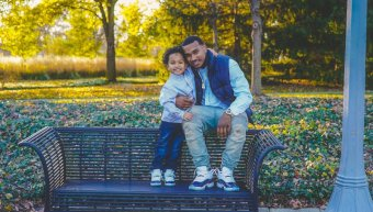 Photo credit Chris Benson. A young black man sitting on a bench embracing a young child