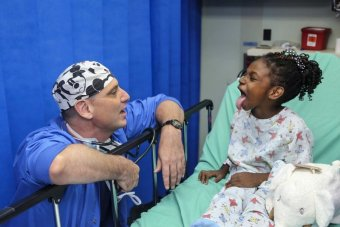 A young black girl in a hospital bed sticks out her tongue at a middle aged white man in scrubs and a surgical cap who is crouched next to the bed.