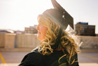 Photo credit: Esther Tuttle. A white woman, in profile, stands wearing a black graduation cap and gown