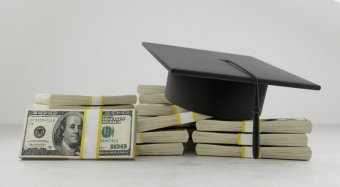A black graduation caps on top of stacks of U.S. $100 bills.