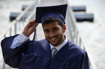 Photo credit: Muhammad Rizwan. A young man wearing a graduation cap and gown smiles at the camera.