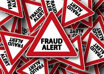 "Several of the same red and white triangular road signs. All of them read ""FRAUD ALERT"""