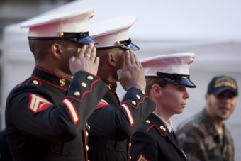 A photo of two men and a woman in U.S. Marine Corps dress uniform, saluting.