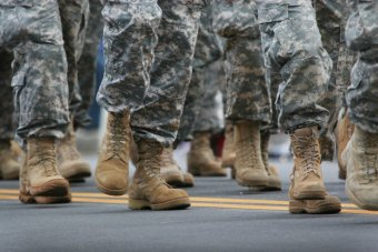 A photo of people, from the knees down, wearing camoflague uniforms and tan combat boots.