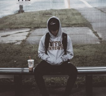 Photo credit: whereslugo. Photo of a young person in a hoodie and baseball cap sits at a bus stop.