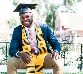 Photo credit: William Stitt. A young black man in a graduation cap and gown sits smiling on a bench in a garden