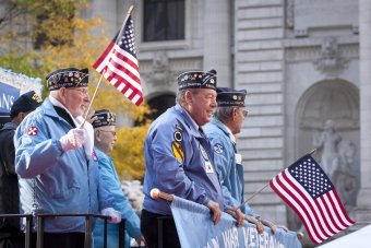 Several older men in Korean War veterans caps march in a parade