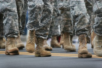 Photo of people in camoflague pants and tan combat boots, from the knee down